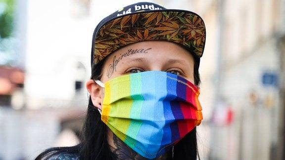 Junge Frau mit Tattoos und Regenbogen-Mundschutz