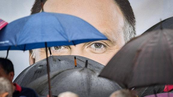 Andrzej Duda auf Plakat, vor dem Personen mit Regenschirmen zu sehen sind