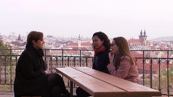 Drei Frauen sitzen in Biergarten und blicken über Prag