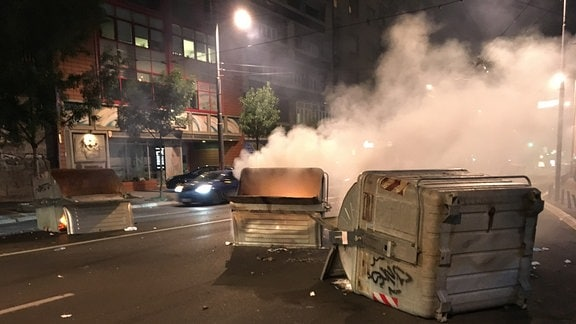 Umgestürzte und angezündete Mülltonnen auf nächtlicher Straße