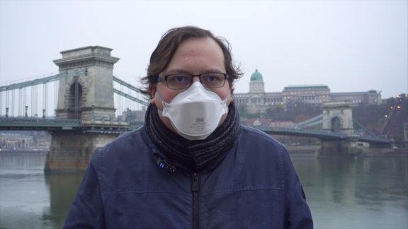 Mann mit Maske am Ufer der Donau in Budapest