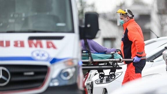 Mann in Schutzkleidung bei einem Patiententransport