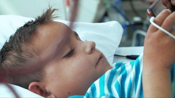 rumänsicher Junge liegt in Klinikbett zur Dialyse und schaut aufs Handy