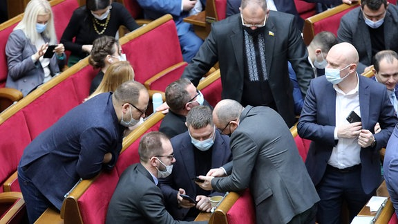 Parlamentarier schauen auf ihre Handys