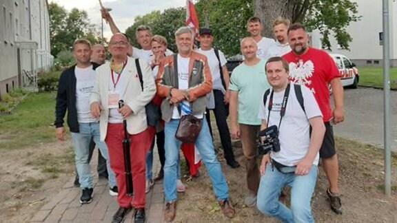 Janusz Zagórski mit Menschgruppe un  polnischer Flagge auf Straße