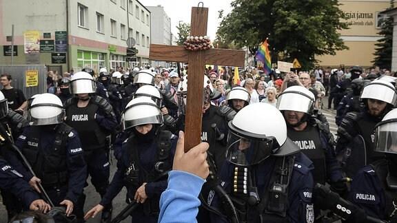 Ein Arm hält ein Holzkreuz, um welches ein Rosenkranz gewickelt ist, bei einem LGBT-Marsch für Gleichberechtigung.