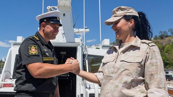 Ein Mann und eine Frau, beide in Uniform, geben sich die Hand