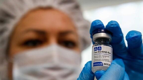 Eine Frau hält eine Ampulle Impfstoff in die Kamera