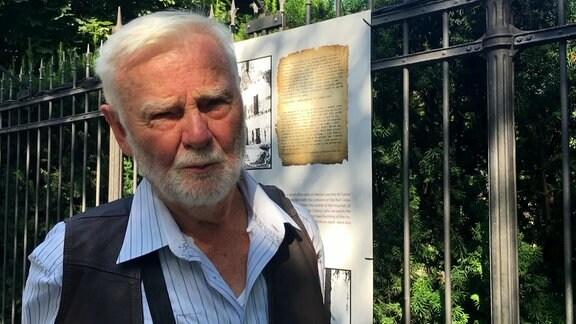 Jan Tyszler steht vor Gartenzaun.