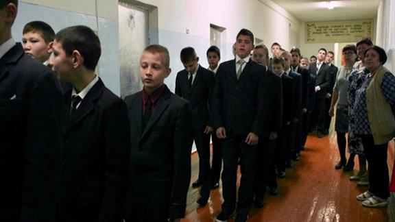 Schüler in russischem Umerziehungsanstalt laufen im Gleichschritt über den Gang