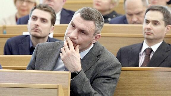 Vitali Klitschko hört mit anderen Menschen einem Vortrag zu.
