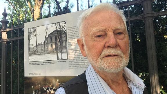 Ein älterer Mann neben einem Zaun