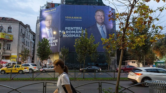 Straßenszene - Fußgänger laufen an einem Wahlplakat in Bukarest vorbei, das Klaus Iohannis zeigt