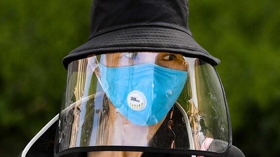 Eine Frau trägt einen Hut, eine Maske und ein Schild.