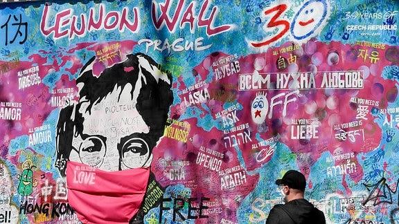 Gesprühtes John Lennon Porträt an einer Mauer in Prag trägt einen Mundschutz