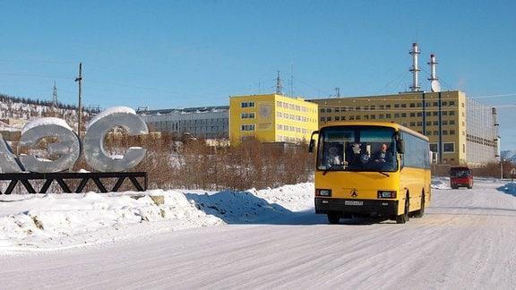 Ein gelber Bus fährt auf einer weiten, schneebedeckten Straße am Gebäude des Bilibino Atomkraftwerks vorbei.