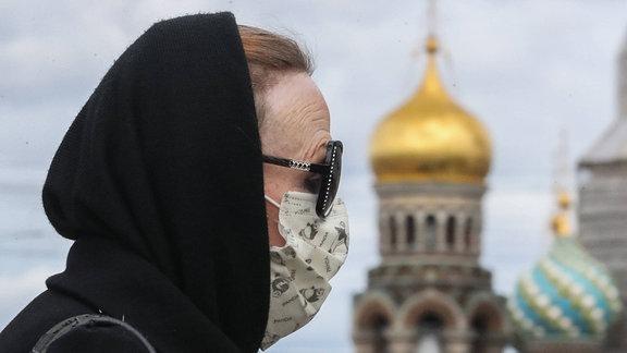 Frau mit Sonnenbrille und Mundschutz