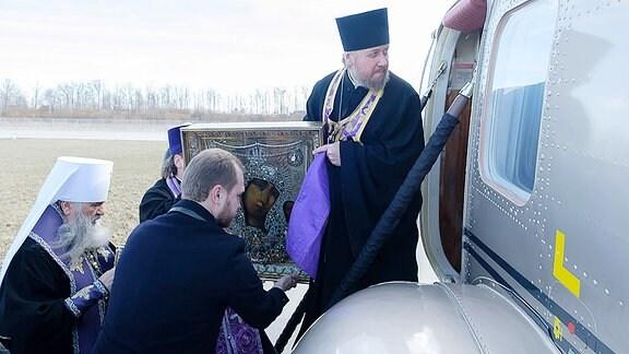 Geistliche besteigen einen Hubschrauber mit einer Ikone.