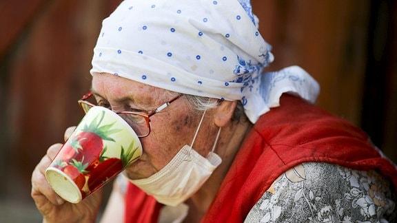 Frau mit Mundschutz auf Datscha in Gorki
