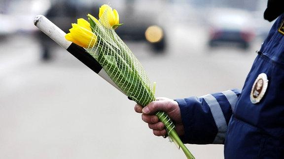 Polizist hält Verkehrsstab und Tulpen