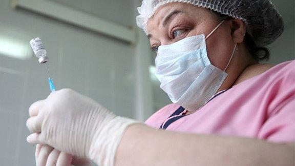 Eine Krankenschwester zieht eine Spritze mit dem Impstoff auf.