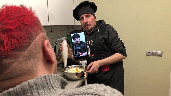 Ein Smartphone auf einem Selfie-Stick filmt einen Mann mit schwarzer Kochmütze und Schürze, der auf dem Display und im Hintergrund zu erkennen ist. Im Vordergrund  sind Kopf und Schultern des Mannes zu sehen, der den Koch filmt.