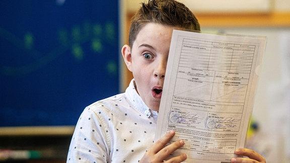 Ein Schuljunge hält sein Zeugnis am Ende des Schuljahres in der Hand.