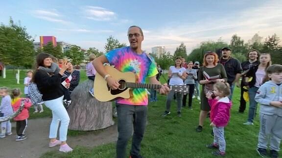 Mann in buntem Shirt spielt Gitarre in einem Park, umringt von singendne Erwachsenen und Kindern.