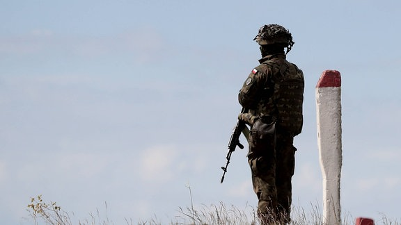 Soldat steht auf einer Anhöhe