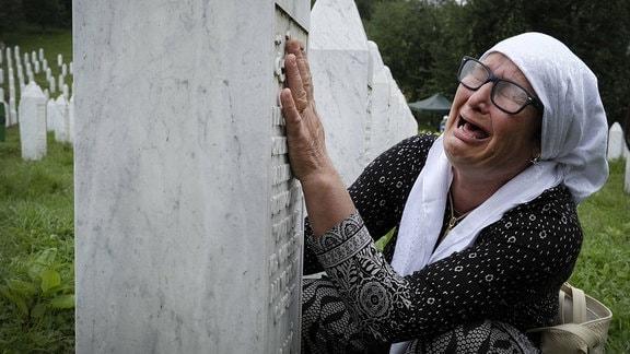 Frau weint an einem Grabstein
