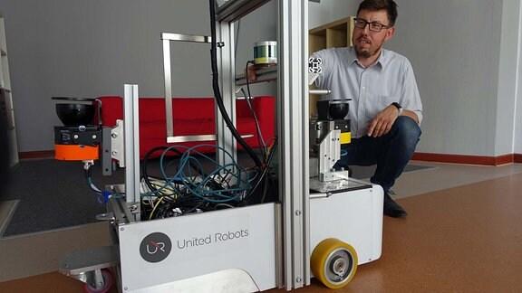 Mann mit Brille hockt vor Robotermodell.