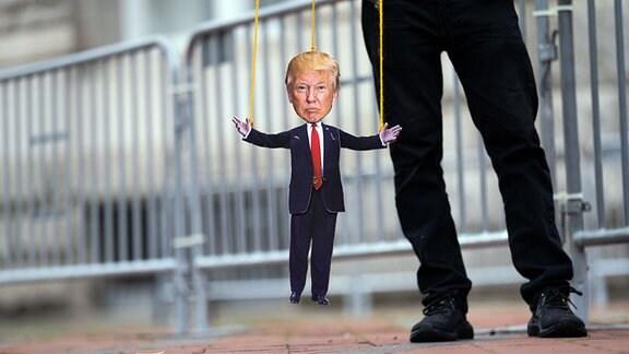 Ein Mann hält eine Donald Trump Marionette
