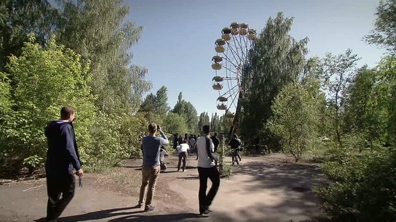 Menschen fotografieren ein gelbes Riesenrad