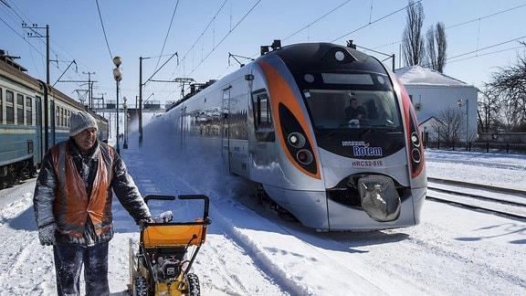 Ein Mann räumt Schnee auf einem Bahnsteig