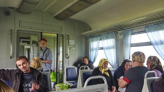 Passagiere sitzen im Abteil eines Zuges