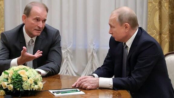 Viktor Medwedtschuk, prorussischer Politiker der Ukraine (l) und Oligarch, spricht mit Wladimir Putin, Präsident von Russland, bei einem gemeinsamen Treffen.