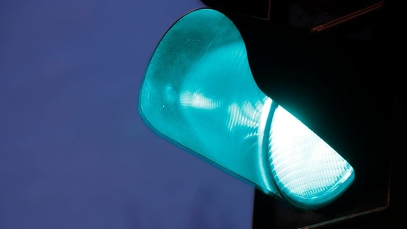 Auf grün geschaltete Verkehrsampel bei Abenddämmerung.