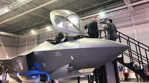 Besucher auf einem Kampfjet.