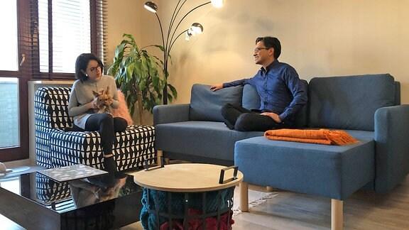 Ein dunkelhaariger Mann und eine Frau mit Brille sitzen mit einer Katze auf einer Couch