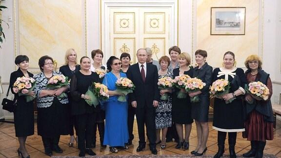 Russlands Präsident Wladimir Putin (Mitte) und Frauen posieren für ein Gruppenfoto während einer Teeparty im Moskauer Kreml am Internationalen Frauentag am 8. März.