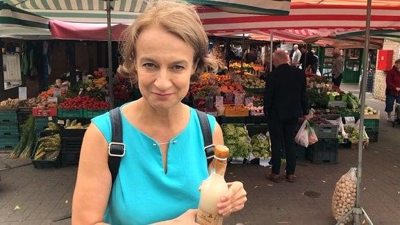 Frau in blauem Kleid steht auf Wochenmarkt und hält Flasche in der Hand