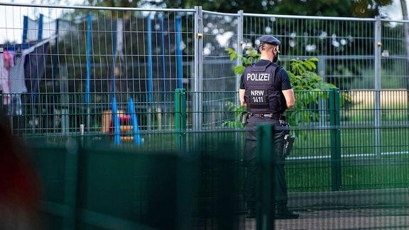 Ein Polizei steht vor einem Zaun