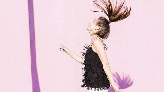 Junge Frau wirft ihren Zopf in die Luft