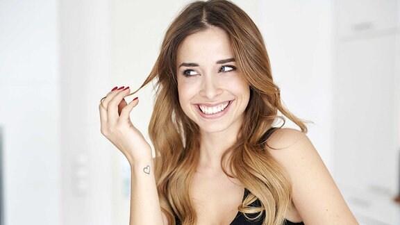 Eine Junge Frau im schwarzen Kleid spielt mit ihren Haaren und lächelt.