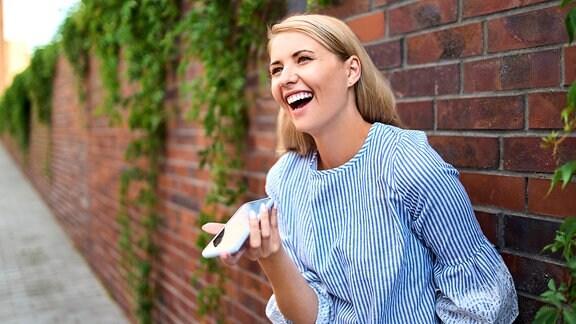 Lachende Frau mit Handy in der Hand