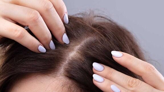 Eine Frau greift sich in ihr dunkles, dünnes Haar.