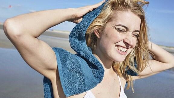 Junge Frau trocknet Haare am Strand mit einem Handtuch.