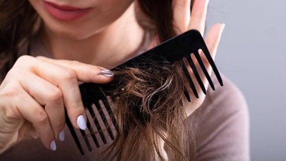 Frau kämmt ihr Haar