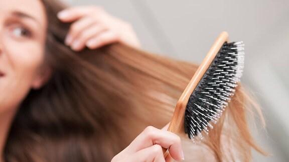 Frau bürstet ihr Haar