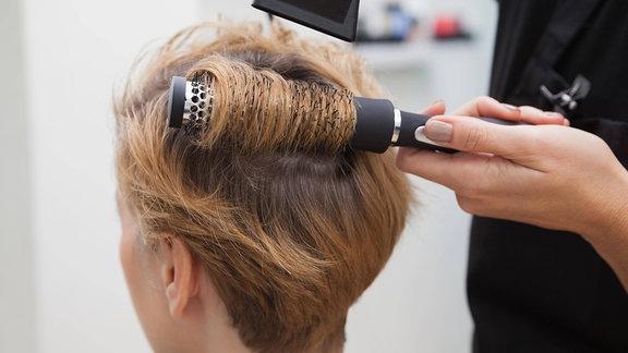 Friseurin föhnt Haare einer Kundin